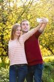 Jeunes couples dans le selfie de prise extérieur d'amour Photos stock