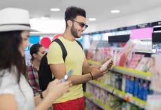 Jeunes couples dans le supermarché choisissant des produits cosmétiques de achat de sourire heureux d'homme et de femme Photos libres de droits