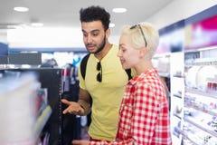 Jeunes couples dans le supermarché choisissant des produits cosmétiques de achat de sourire heureux d'homme et de femme Image stock