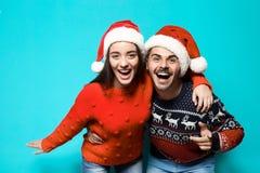 Jeunes couples dans les chandails et des chapeaux chauds de Noël image libre de droits