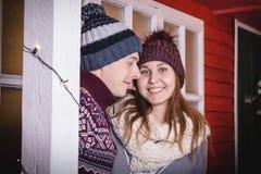 Jeunes couples dans les chandails et des chapeaux ensemble près du mur de la petite maison décoré pendant Mary Christmas et la no Photo stock