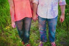 Jeunes couples dans les taches lumineuses de la peinture tenant des mains en nature, peintres, réparation, festival de Holi Images libres de droits