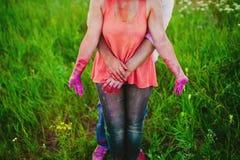 Jeunes couples dans les taches lumineuses de la peinture tenant des mains en nature, peintres, réparation, festival de Holi Photo stock
