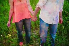 Jeunes couples dans les taches lumineuses de la peinture tenant des mains en nature, peintres, réparation, festival de Holi Photo libre de droits