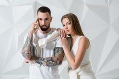 Jeunes couples dans les vêtements décontractés sur le fond blanc Image stock