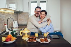 Jeunes couples dans leur cuisine posant avec leurs têtes étroitement ensemble derrière le compteur souriant à la caméra photographie stock