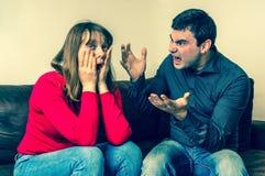 Jeunes couples dans un argument dans le salon photos stock