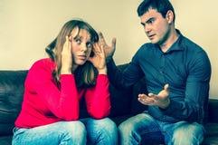 Jeunes couples dans un argument dans le salon photographie stock