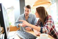 Jeunes couples dans un café websurfing Photo libre de droits