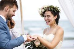 Jeunes couples dans une cérémonie de mariage à la plage Images stock