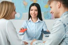 Jeunes couples dans une communication d'agence de visite avec un concept de déplacement d'agent de voyage donnant des documents photographie stock