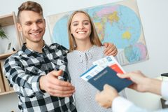 Jeunes couples dans une communication d'agence de visite avec un concept de déplacement d'agent de voyage prenant des documents photographie stock