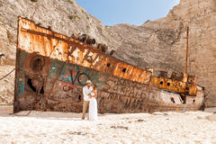 Jeunes couples dans une plage avec le naufrage Images stock