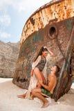 Jeunes couples dans une plage avec le naufrage Image stock