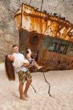 Jeunes couples dans une plage avec le naufrage Photographie stock libre de droits
