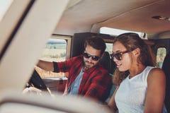 Jeunes couples dans une voiture regardant la carte pour des directions Images libres de droits
