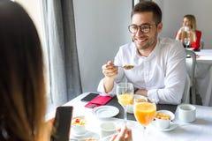 Jeunes couples de charme appréciant le petit déjeuner dans la salle à manger de l'hôtel photos stock