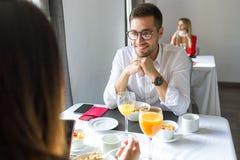 Jeunes couples de charme appréciant le petit déjeuner dans la salle à manger de l'hôtel images libres de droits