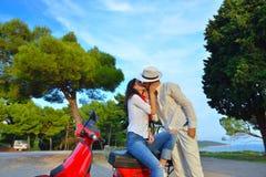 Jeunes couples de cycliste sur la route de campagne contre le ciel Photographie stock libre de droits