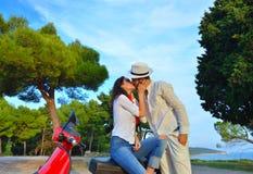 Jeunes couples de cycliste sur la route de campagne contre le ciel Image stock