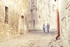 Jeunes couples de déplacement ayant une promenade médiévale sur une vieille rue Image stock