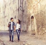 Jeunes couples de déplacement ayant une promenade médiévale sur une vieille rue Photographie stock libre de droits
