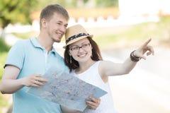 Jeunes couples de déplacement regardant quelque chose pendant le voyage Image stock