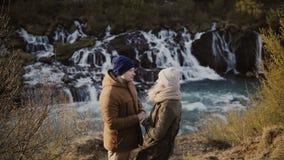 Jeunes couples de déplacement se tenant en vallée de montagnes près des cascades en Islande et regardant sur l'un l'autre, date r clips vidéos