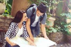 Jeunes couples de déplacement vérifiant la carte Photo stock
