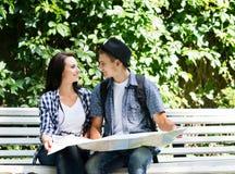 Jeunes couples de déplacement vérifiant la carte en parc Image libre de droits