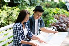 Jeunes couples de déplacement vérifiant la carte en parc Photos libres de droits