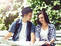 Jeunes couples de déplacement vérifiant la carte en parc Photo libre de droits