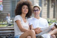 Jeunes couples de déplacement vérifiant la carte sur le banc Photos stock