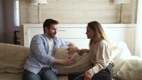 Jeunes couples de famille parlant ayant la conversation se reposant sur le sofa clips vidéos