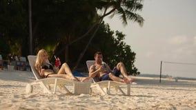 Jeunes couples de famille prenant un bain de soleil et buvant le cocktail coloré sur la plage tropicale Amants sur la lune de mie clips vidéos