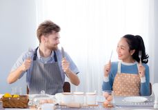 Jeunes couples de famille se reposant à la table dans la cuisine et tenant la cuillère et la fourchette ensemble Image stock