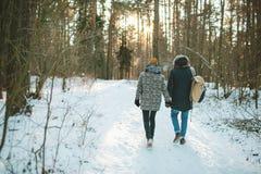 Jeunes couples de hippie ayant une promenade dans la forêt d'hiver Photographie stock libre de droits