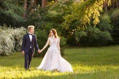 Jeunes couples de jeunes mariés dans un jardin de floraison Image stock