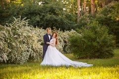 Jeunes couples de jeunes mariés dans un jardin de floraison Photos libres de droits