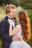 Jeunes couples de jeunes mariés dans un jardin de floraison Photos stock