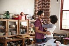 Jeunes couples de métis embrassant dans la cuisine, taille  Image stock