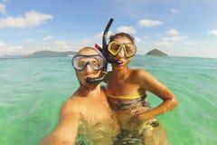 Jeunes couples de métis faisant la photo de Selfie utilisant l'appareil-photo imperméable dans l'océan clair après avoir navigué  Photos stock