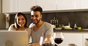 Jeunes couples de métis utilisant la lumière du soleil de matin d'ordinateur portable, femme asiatique d'homme hispanique heureux banque de vidéos