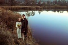 Jeunes couples de mariage appréciant des moments romantiques dans le lac d'automne Images stock