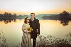 Jeunes couples de mariage appréciant des moments romantiques dans le lac d'automne Photographie stock libre de droits
