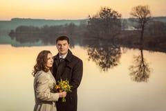 Jeunes couples de mariage appréciant des moments romantiques dans le lac d'automne Image libre de droits