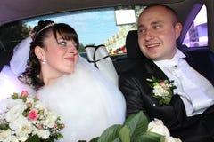 Jeunes couples de mariage dans la voiture Photos stock
