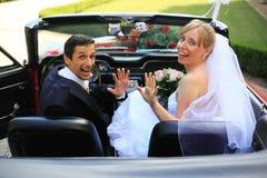 Jeunes couples de mariage dans le véhicule de cabriolet Image stock