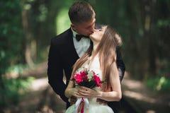 Jeunes couples de mariage, jeunes mariés posant sur une voie de chemin de fer Photographie stock libre de droits