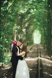 Jeunes couples de mariage, jeunes mariés posant sur une voie de chemin de fer Images stock
